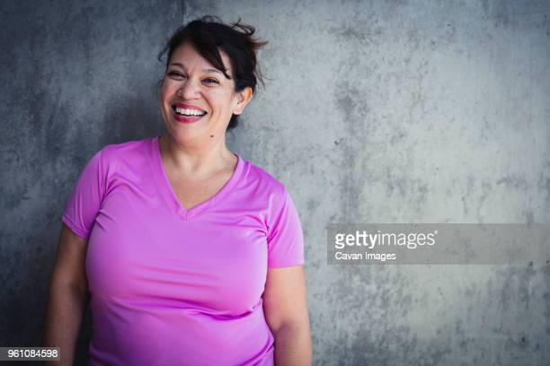 portrait of cheerful woman standing against wall in yoga studio - dikke vrouw stockfoto's en -beelden