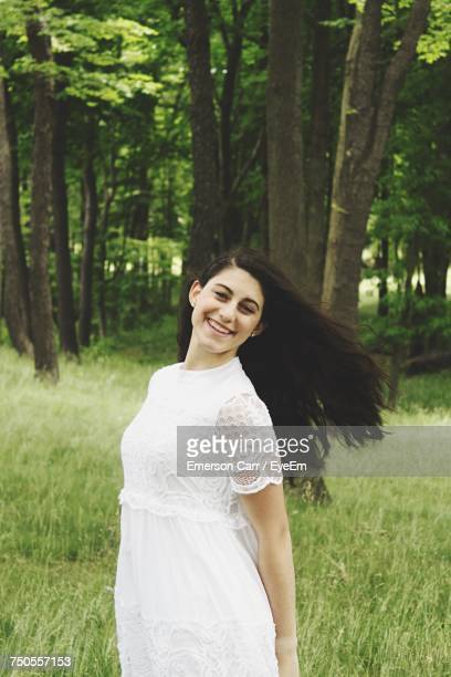 portrait of cheerful woman standing on grassy field - head cocked stock pictures, royalty-free photos & images