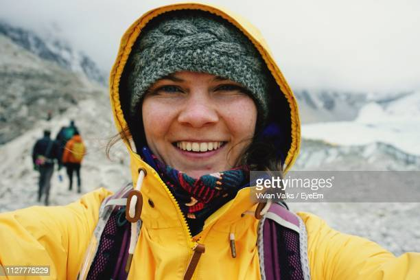 portrait of cheerful woman wearing yellow jacket during winter - yellow hat stock pictures, royalty-free photos & images