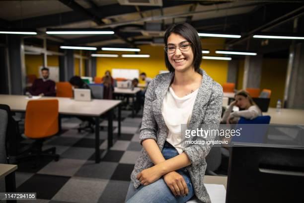 retrato de mujer alegre con anillo de la nariz en el trabajo - grupo mediano de personas fotografías e imágenes de stock