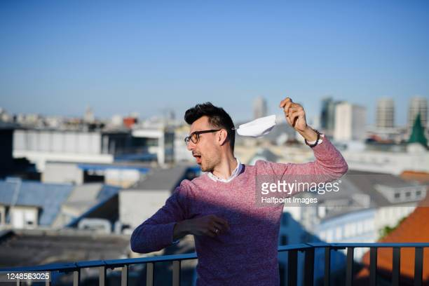 portrait of cheerful young businessman standing outdoors in city, holding face mask. - entfernt stock-fotos und bilder