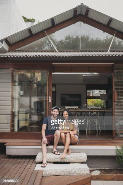 Portrait of cheerful young couple sitting on step outside house smiling