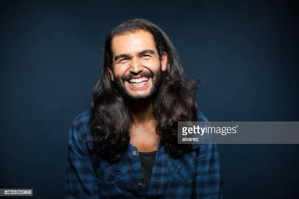 Portrait Of Cheerful Young Man With Long Hair