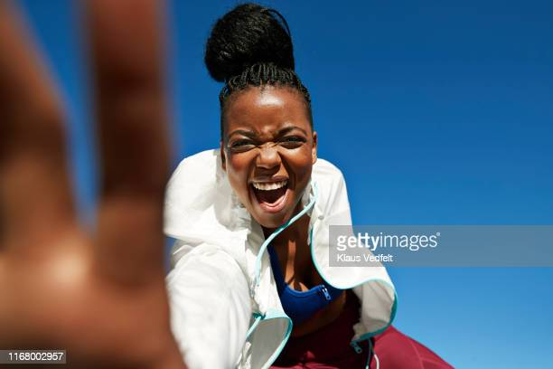 portrait of cheerful young sportswoman with hair bun against clear blue sky - athlete stock pictures, royalty-free photos & images
