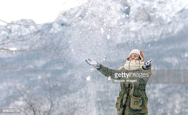 Portrait of cheerful young woman having fun on snow mountain