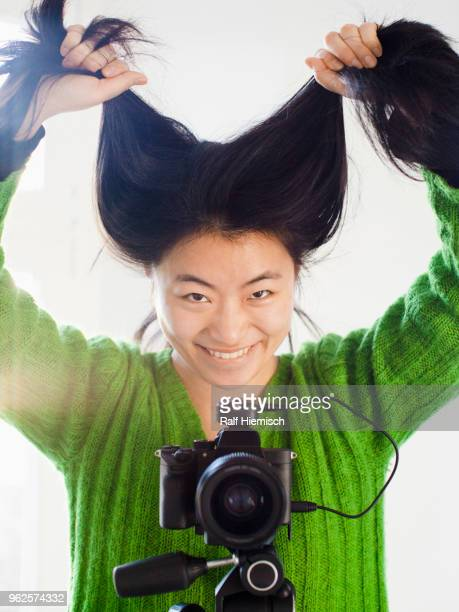 Portrait of cheerful young woman holding hair while standing with camera