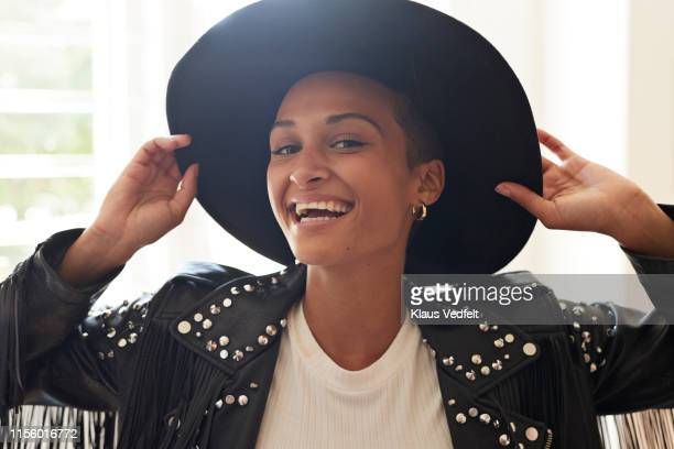portrait of cheerful young woman holding hat - black hat stock pictures, royalty-free photos & images