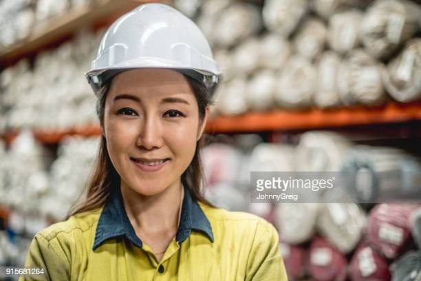 Portrait of cheerful young woman in hard hat