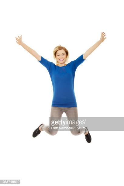 portrait of cheerful young woman jumping against white background - human arm stock pictures, royalty-free photos & images