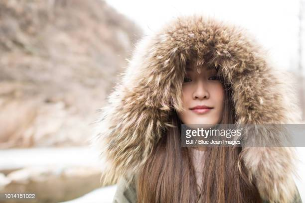 Portrait of cheerful young woman outdoors in winter