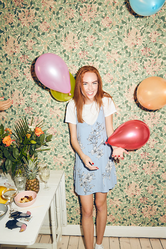 Portrait of cheerful young woman standing amidst balloons by table against wallpaper during party at home - gettyimageskorea
