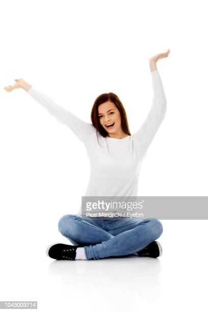 portrait of cheerful young woman with arms raised sitting against white background - piernas cruzadas fotografías e imágenes de stock