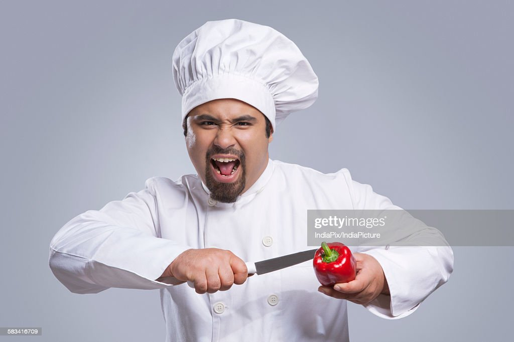 Portrait of chef cutting capsicum with knife : Stock Photo