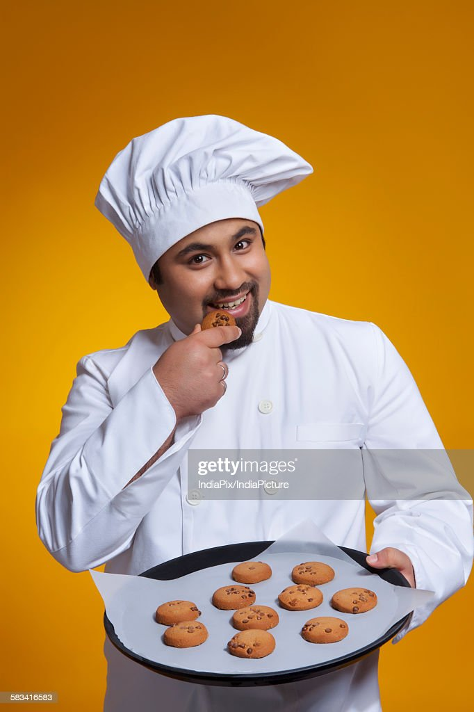 Portrait of chef eating a cookie : Stock Photo