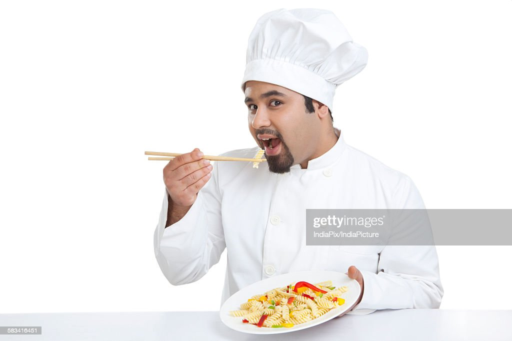 Portrait of chef eating pasta with chopsticks : Stock Photo
