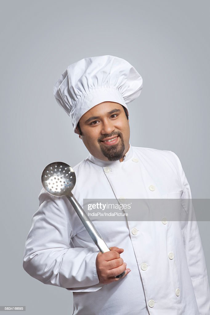 Portrait of chef holding a skimmer : Stock Photo