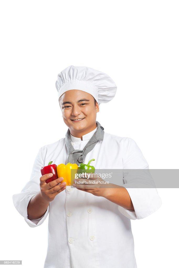 Portrait of chef holding capsicum : Stock Photo