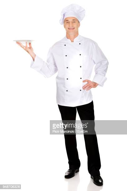 Portrait Of Chef Holding Plate While Standing Against White Background