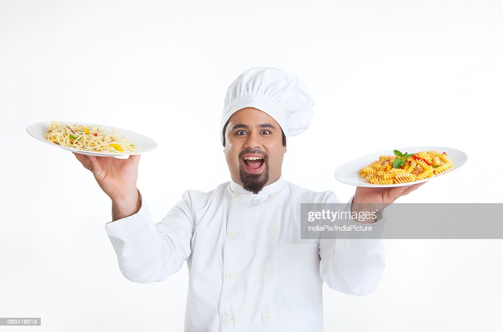 Portrait of chef holding plates with pasta : Stock Photo