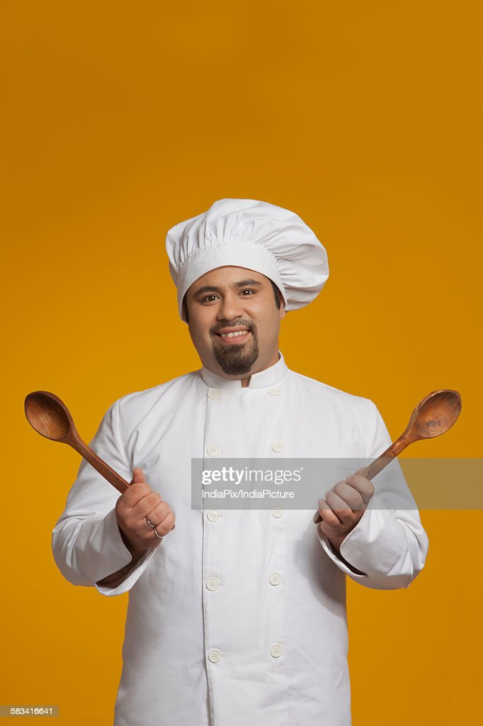 Portrait of chef holding wooden spoons : Stock Photo