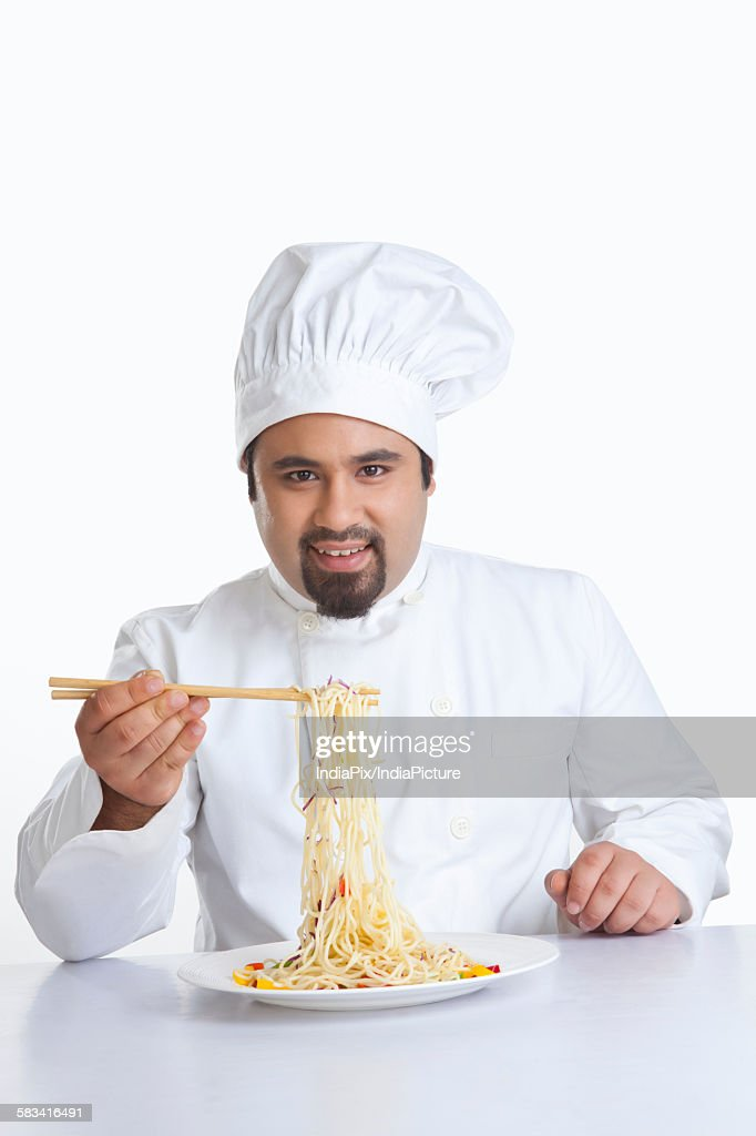 Portrait of chef lifting pasta with chopsticks : Stock Photo