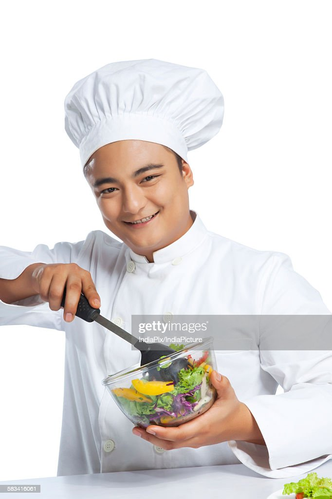 Portrait of chef mixing vegetables in bowl : Stock Photo