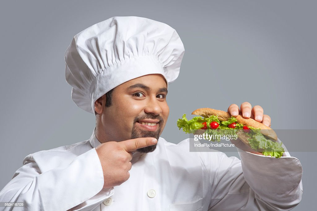 Portrait of chef pointing at sandwich : Stock Photo