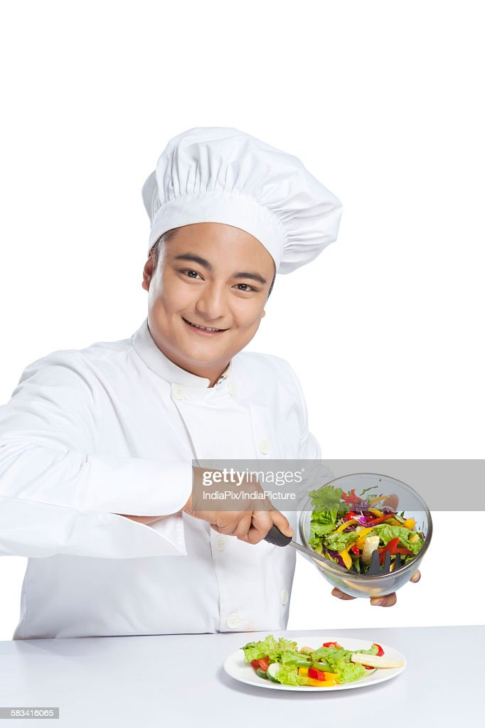 Portrait of chef serving vegetables on plate : Stock Photo
