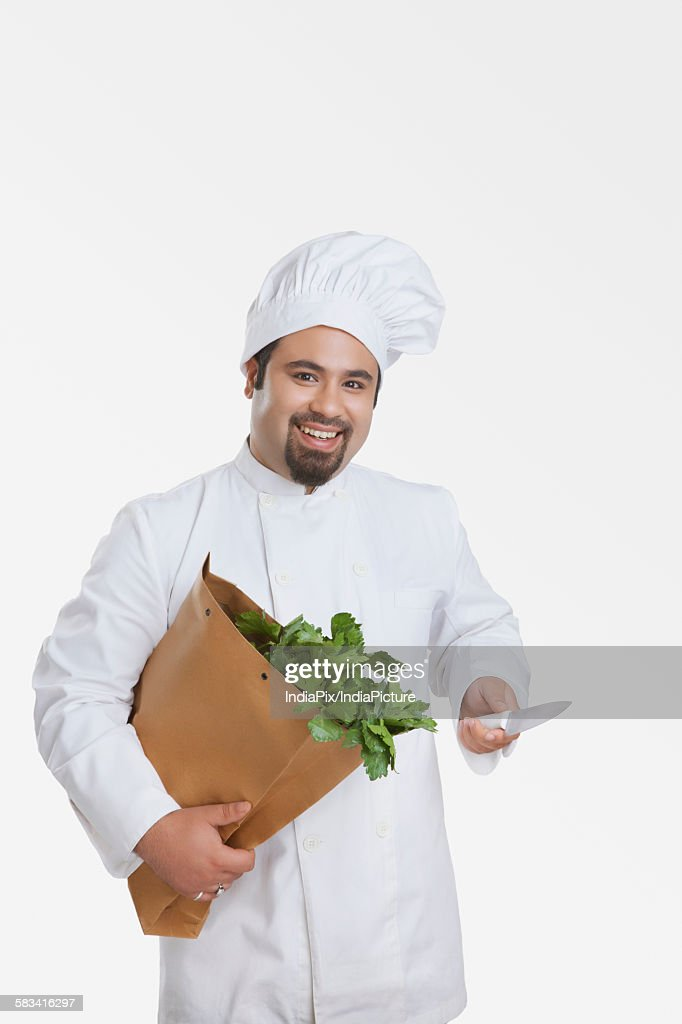 Portrait of chef with bag of vegetables and knife : Stock Photo