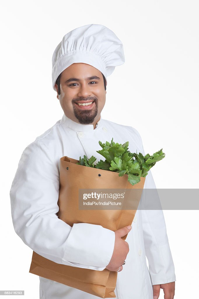 Portrait of chef with bag of vegetables : Stock Photo