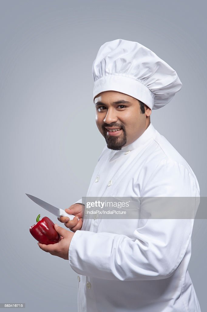 Portrait of chef with capsicum and knife : Stock Photo