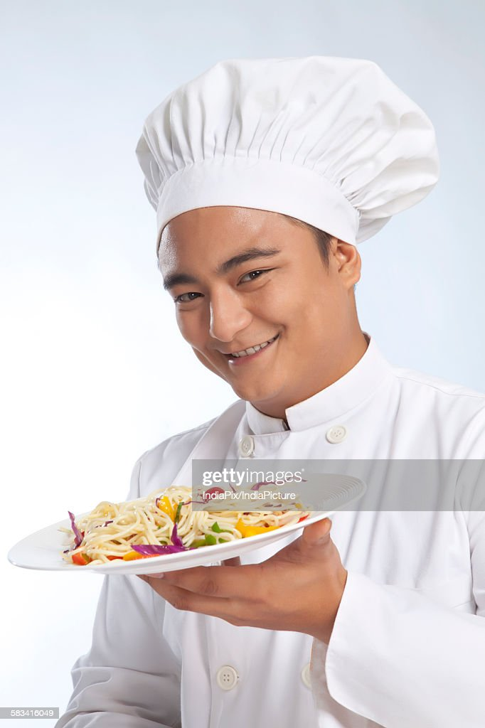 Portrait of chef with plate of noodles : Stock Photo