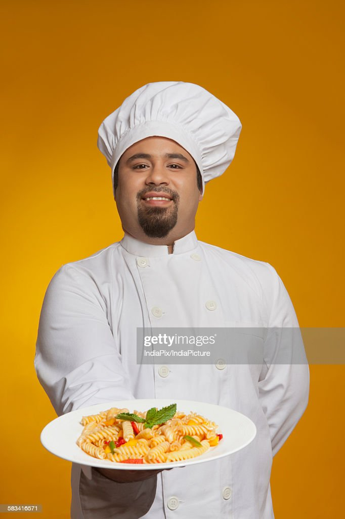 Portrait of chef with plate of pasta : Stock Photo