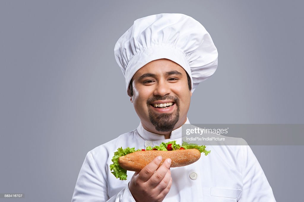 Portrait of chef with sandwich smiling : Stock Photo