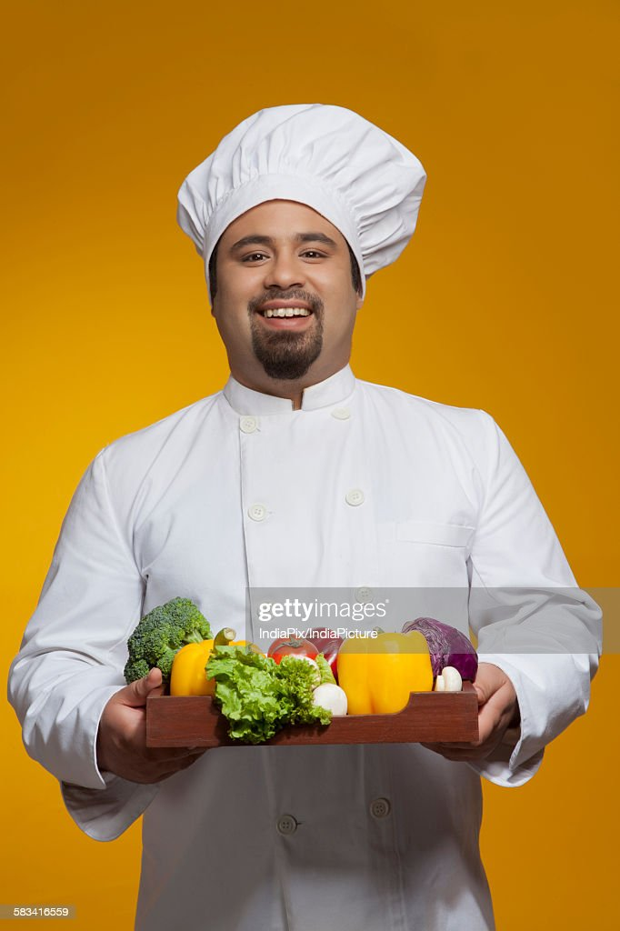 Portrait of chef with tray of vegetables : Stock Photo