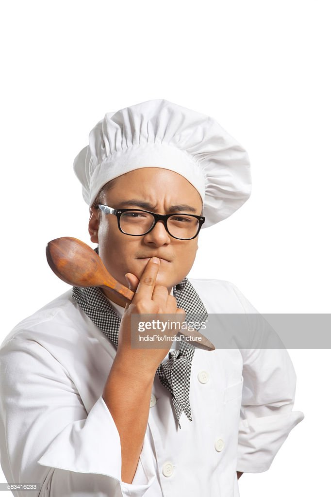 Portrait of chef with wooden spoon thinking : Stock Photo