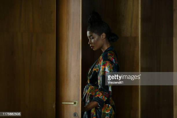 portrait of chic woman wearing patterned dress at a wooden door - only mid adult women stock pictures, royalty-free photos & images