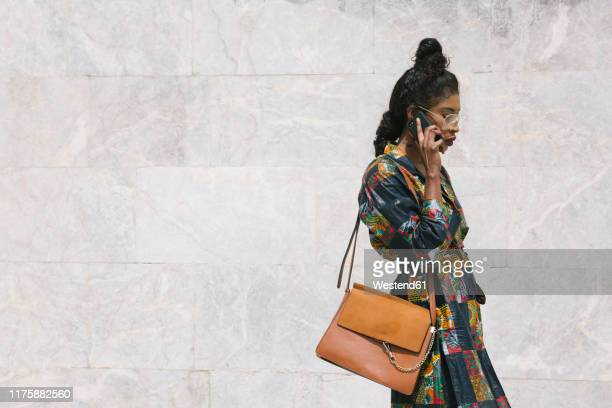 portrait of chic woman wearing patterned dress talking on cell phone - ショルダーバッグ ストックフォトと画像