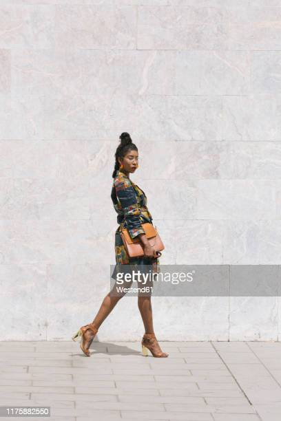 portrait of chic woman wearing patterned dress walking outdoors - multi colored dress stock pictures, royalty-free photos & images
