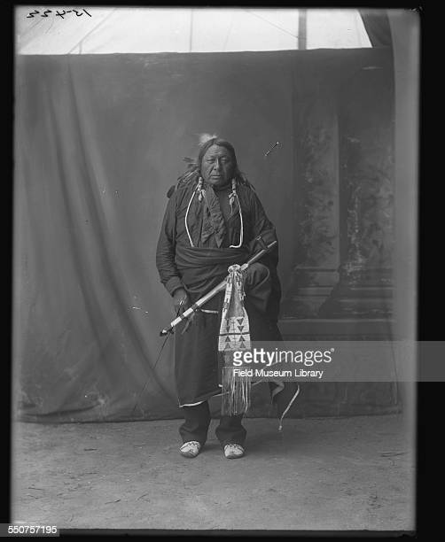 Portrait of Chief Bushy Head a Native American Cheyenne holding a beaded pipe bag and pipe wearing beaded moccasins with long yarn wrapped hair a...