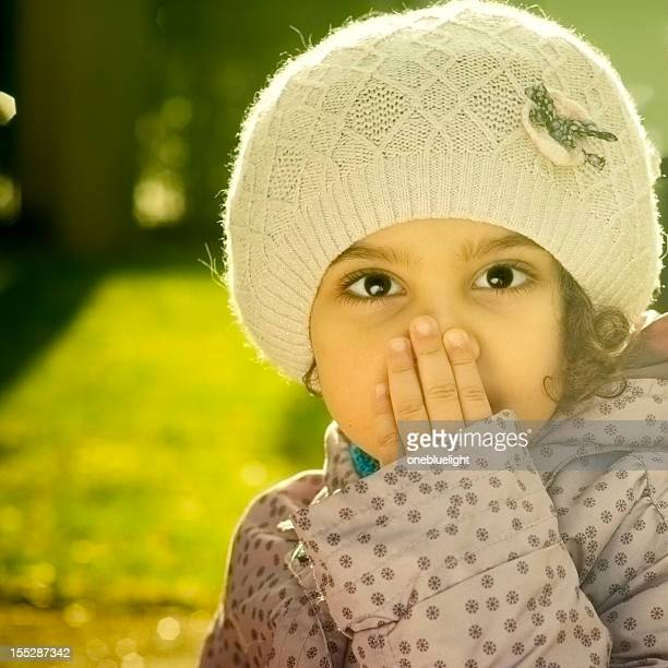 Portrait of Child (4-5) Covering Mouth with Her Hand