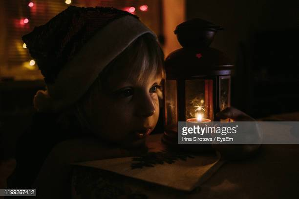 portrait of child in santa's hat near candle in illuminated room at night - christmas decore candle stock pictures, royalty-free photos & images