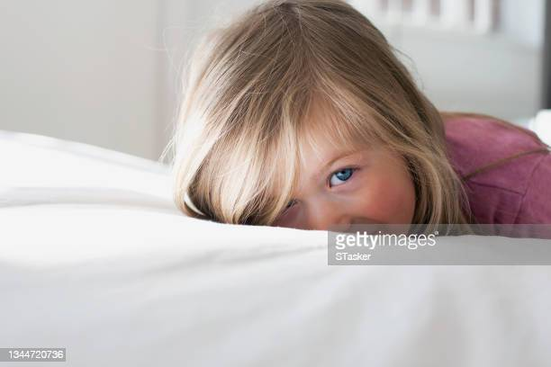 portrait of child lying on bed - st. albans stock pictures, royalty-free photos & images