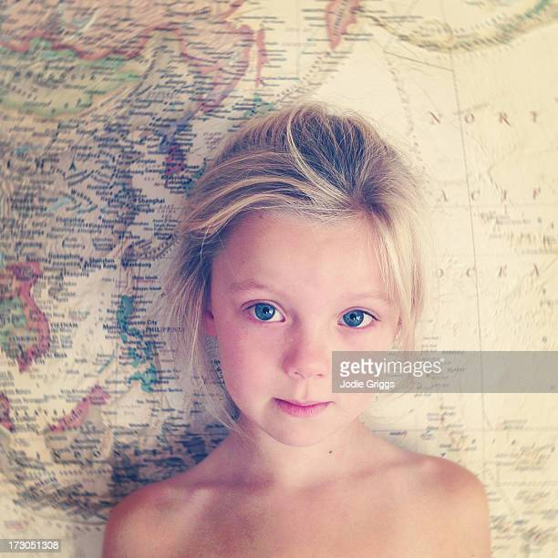 Portrait of child standing in front of world map