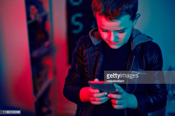 Portrait of child typing on mobile phone and looking at the screen at night