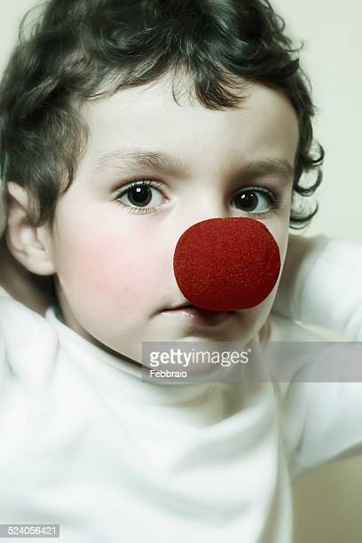 portrait of child with a red clown nose - clown's nose stock photos and pictures