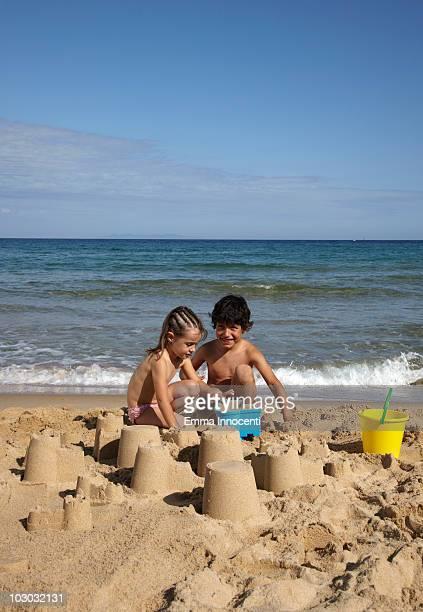 portrait of children building sand castle on beach - petite fille culotte photos et images de collection