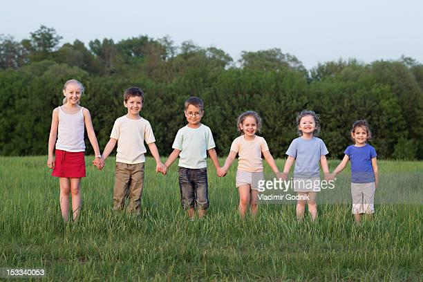 portrait of children holding hands in a field - lang lengte stockfoto's en -beelden
