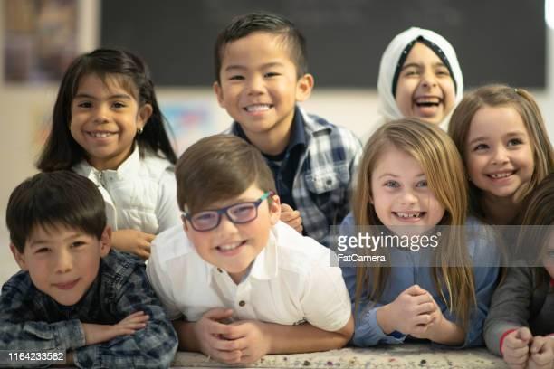 retrato das crianças que encontram-se para baixo no sorriso da escola - hijab - fotografias e filmes do acervo