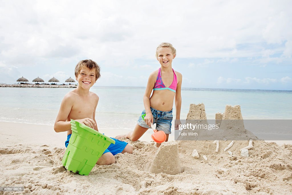 Portrait of children (10-12) playing on beach in sand : Foto de stock
